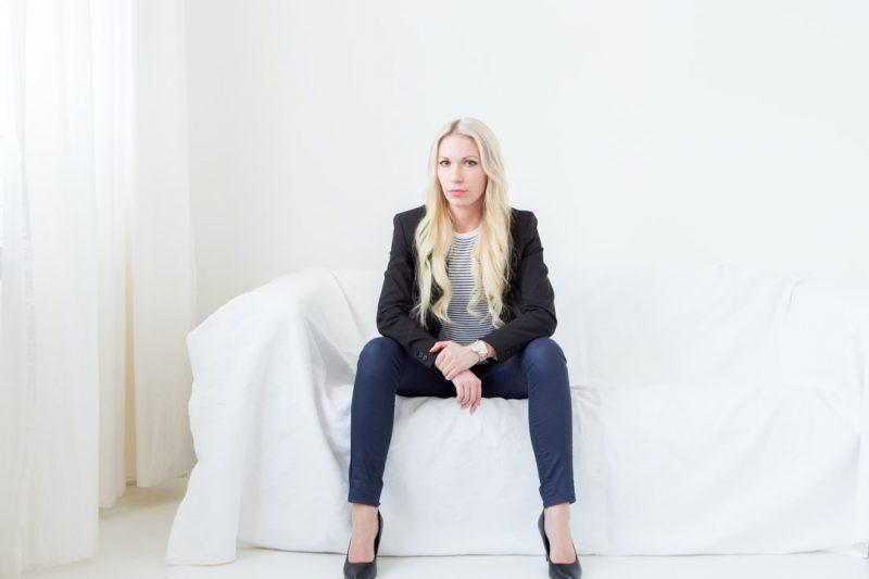 Kvinna sitter på vit soffa