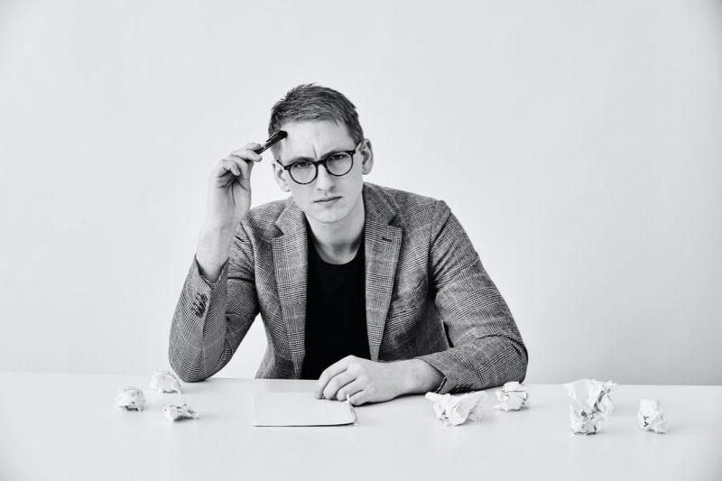 Man med kavaj och glasögon pekar en penna mot pannan